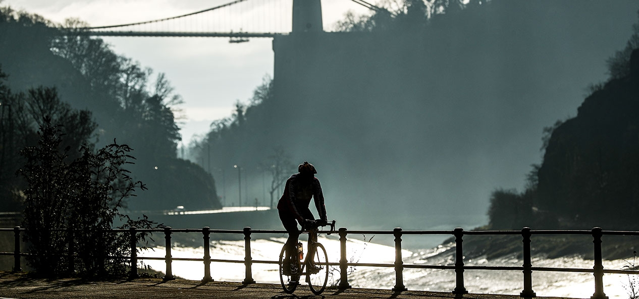 A person rides their bike by the River Avon in Bristol