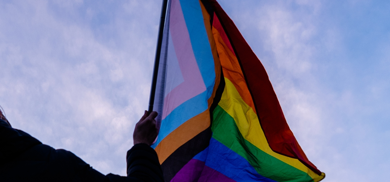 A person waves the progress pride flag