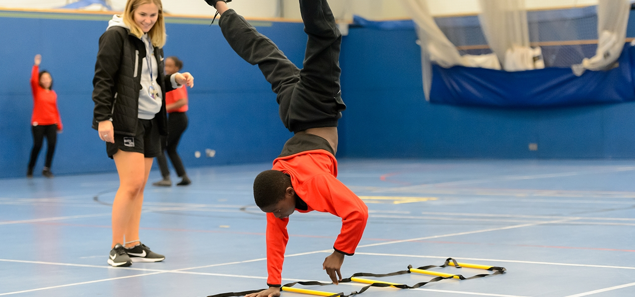 A boy performs a cartwheel in a school PE lesson