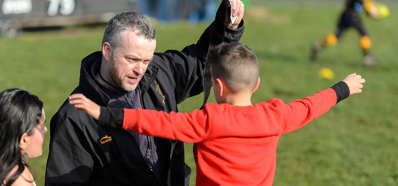 A coach puts tag rugby straps on a child