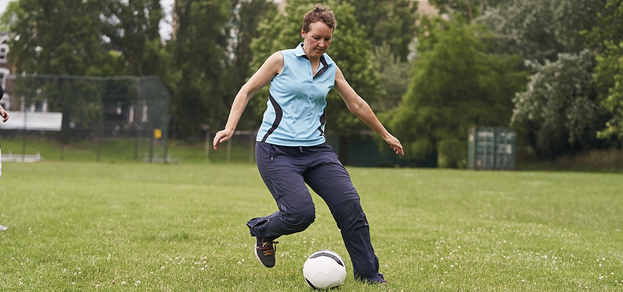 A woman playing football in the park