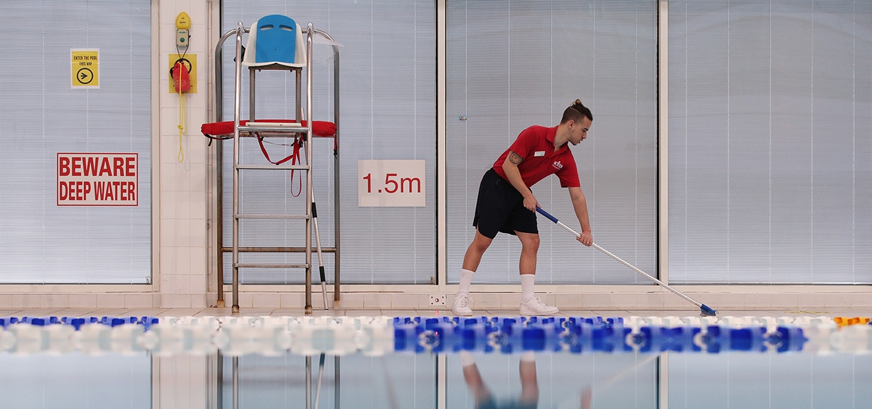 A man cleans the side of an indoor swimming pool