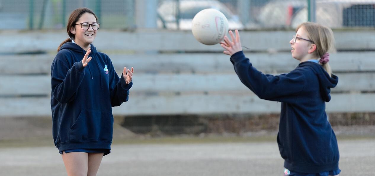 A schoolgirl throws a ball towards another girl during an outdoor game of netball.