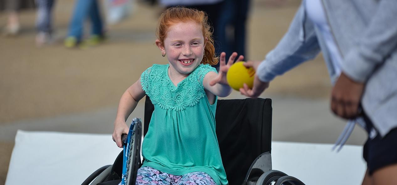 A girl in a wheelchair takes a tennis ball from a coach
