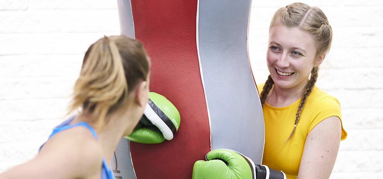 Two women at boxing training working out on a heavy bag