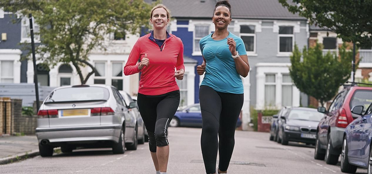 Two women run side-by-side down a road.