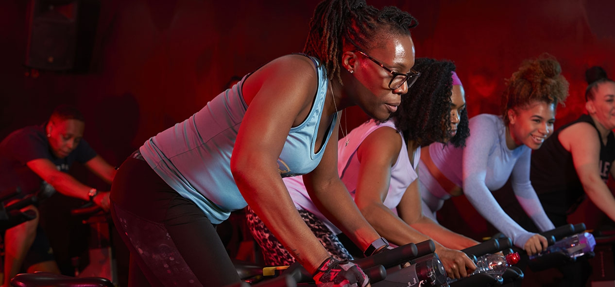 A group of women take part in a spin class at a gym.