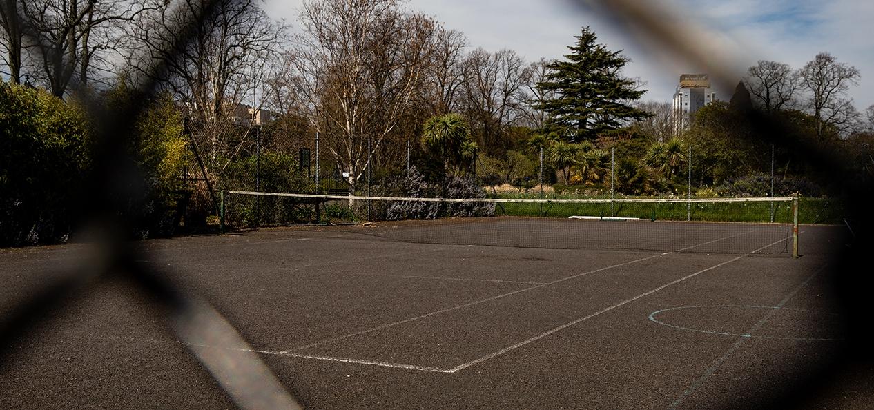 An empty tennis court captured through a wire fence.