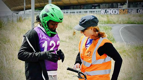 A volunteer speaks to a teenage BMX rider