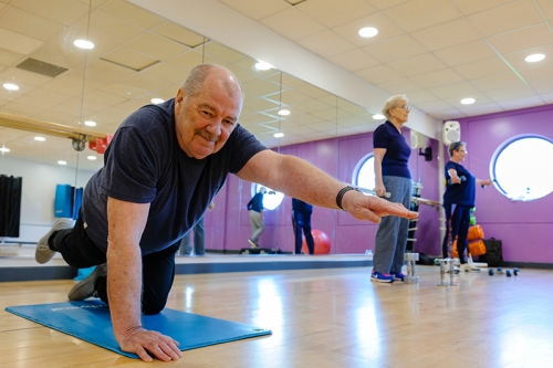 Cotman Housing Association - an older man stretches on an exercise mat in an exercise studio