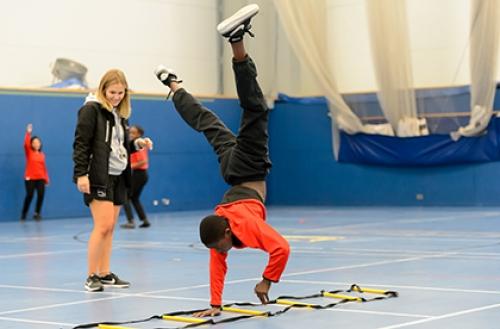 A boy performs a cartwheel in a school PE lesson