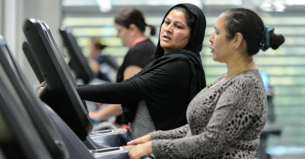 Two women on exercise machines inside a gym.