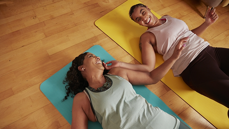 Two women lying down on yoga mats.
