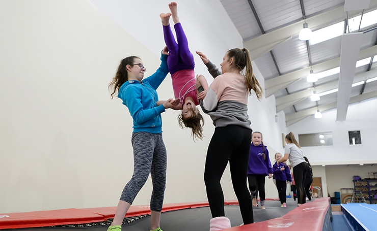 A young gymnast getting some help as she practises vaulting.