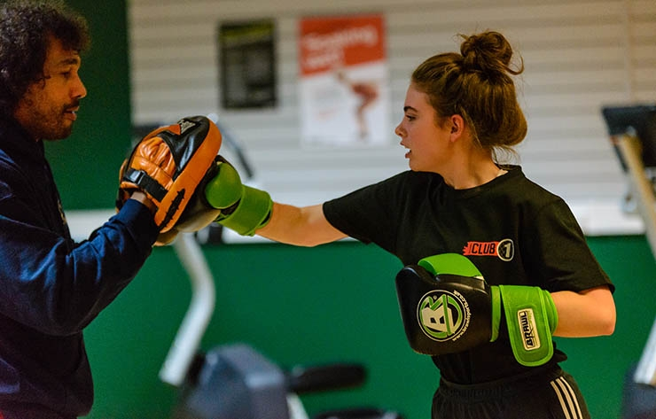 A girl boxing inside a sports hall.