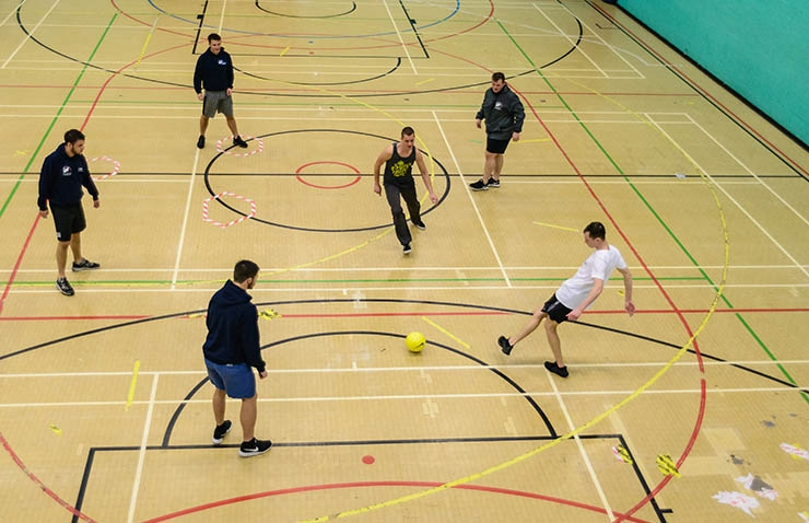 An overhead shot of a group of people playing football in a sports hall.