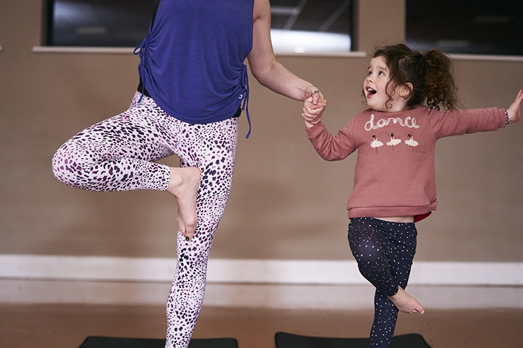 A woman and her daughter do yoga together
