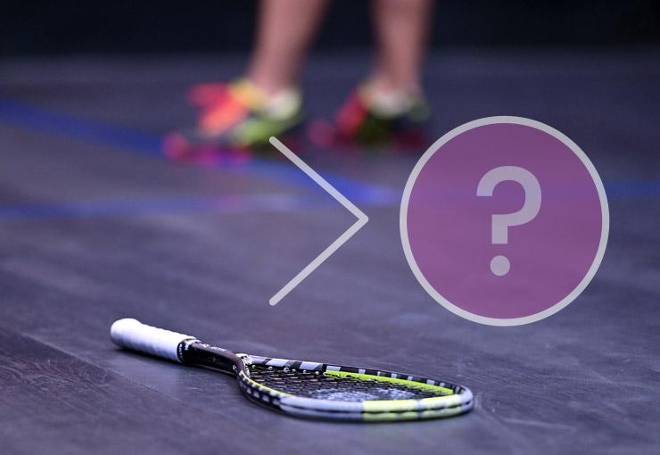 壁球场的地板上的壁球球拍,顶部有一个问号的图形覆盖物。