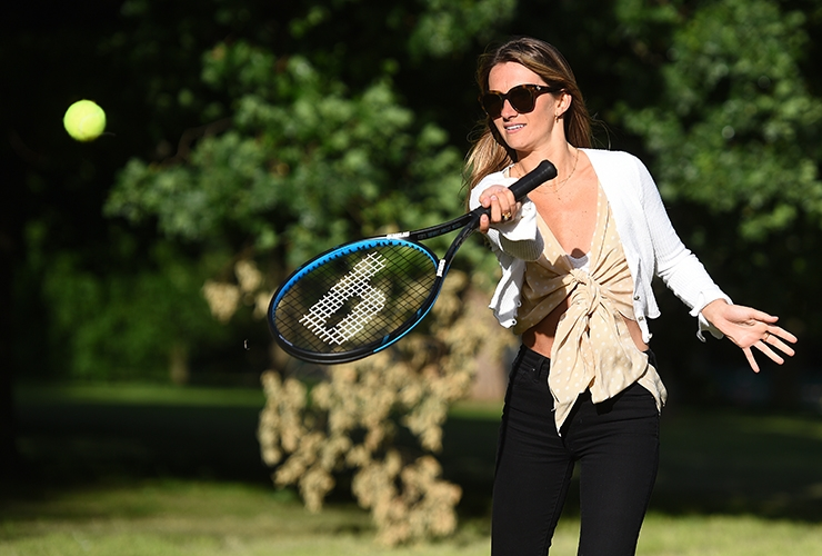 A women enjoys a casual game of tennis in the park