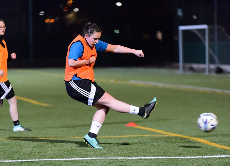 A woman kicking a football while playing on an outdoors pitch.