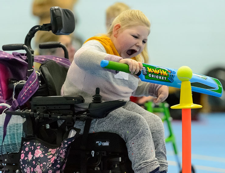 A girl with cerebral palsy, in a wheelchair, hits a ball with a cricket bat, from a tee