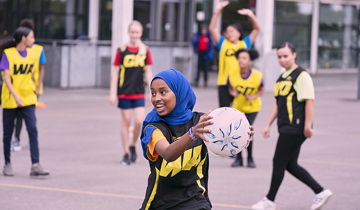 A girl playing netball on an outdoor court.