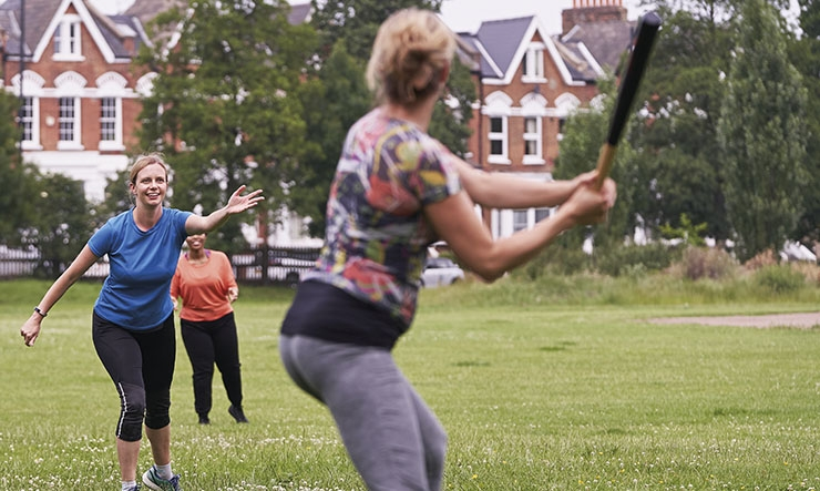 Women playing a game of rounders in a park
