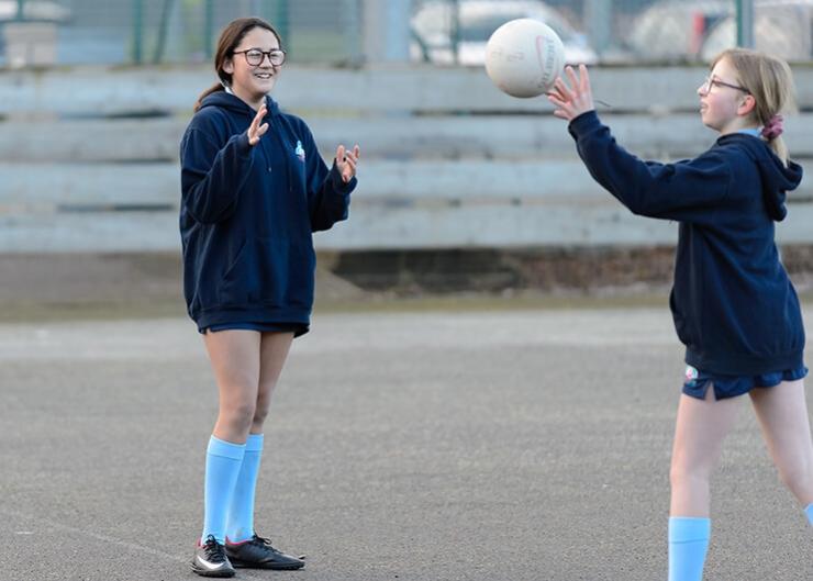 在户外玩无挡板篮球时,一个女学生把球扔向另一个女孩。