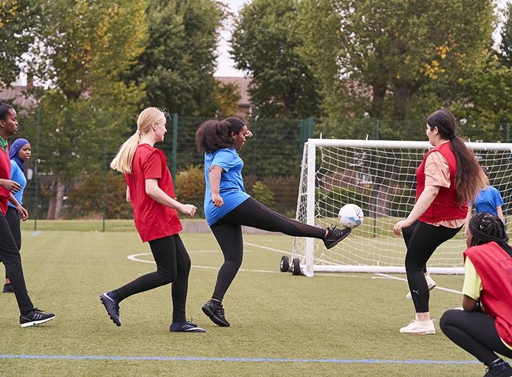 A woman kicks the ball towards goal during an outdoor game of football.