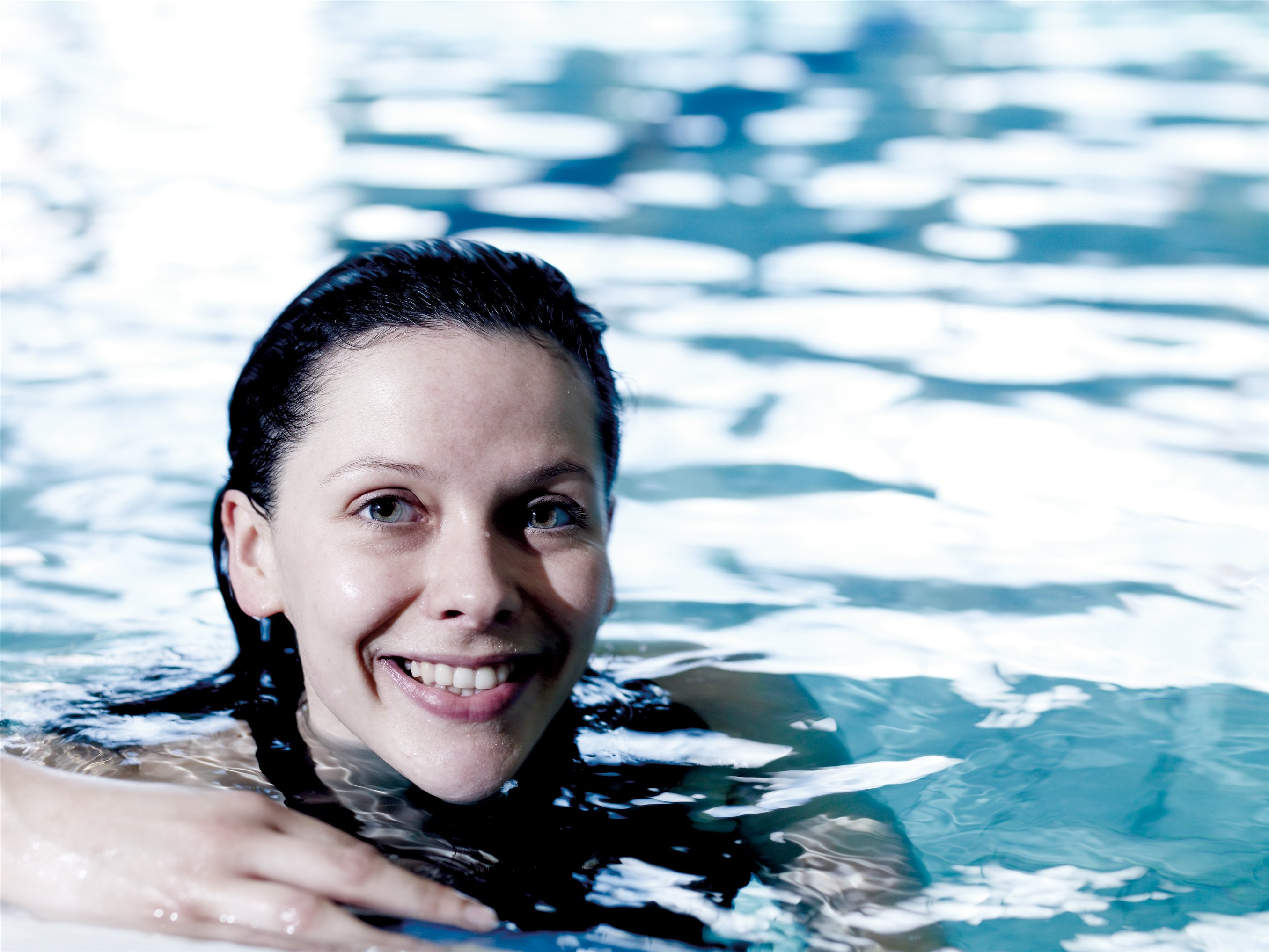 Swimming woman poolside smiling closer
