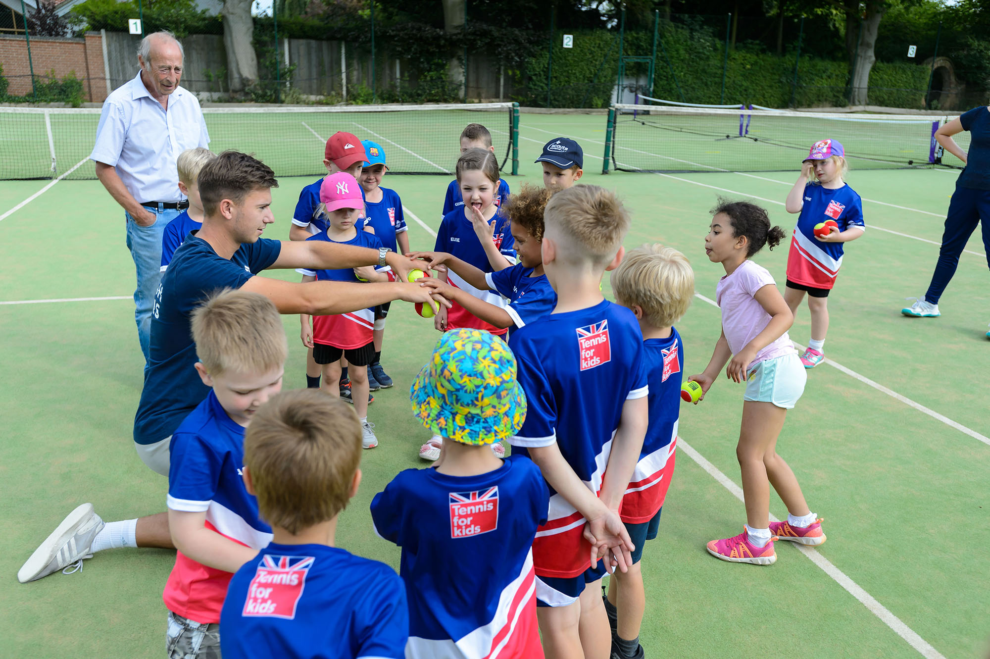 A coach demonstrates a coordination drill at a mini-tennis session