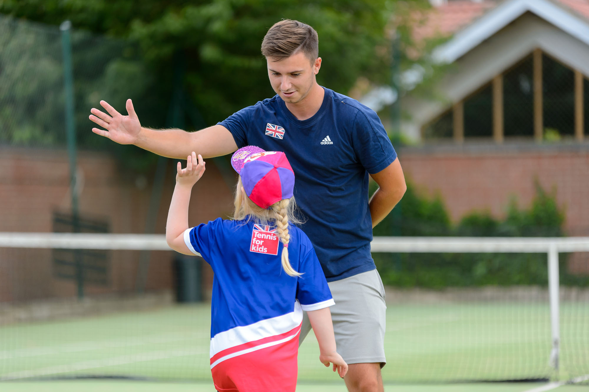 Child and coach high-five at a mini-tennis ession