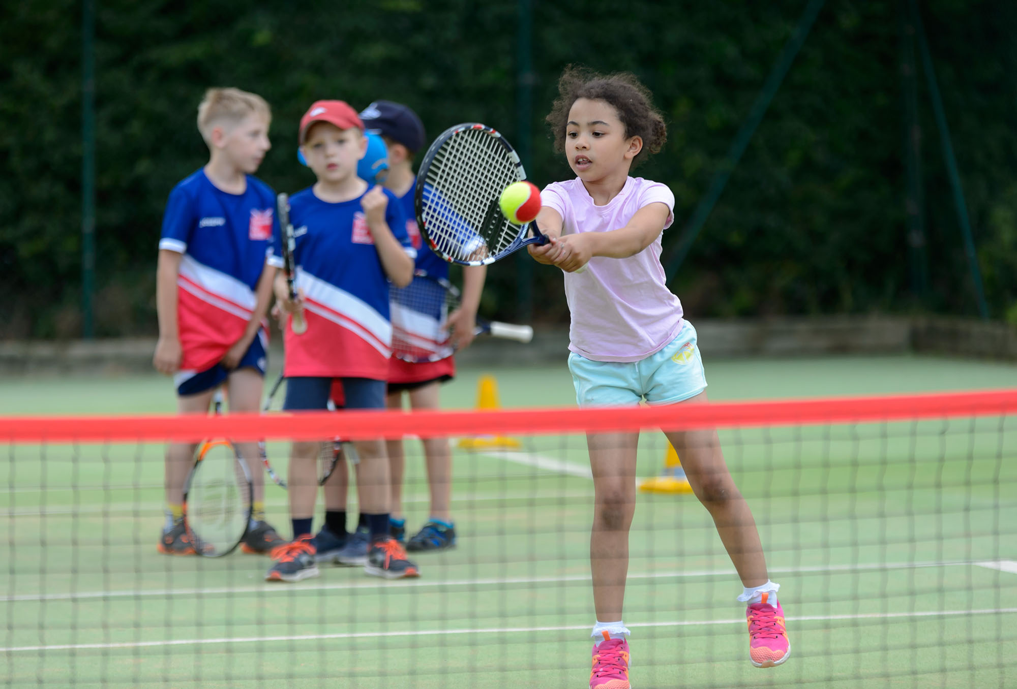 Young girl hits tennis ball at mini-tennis session