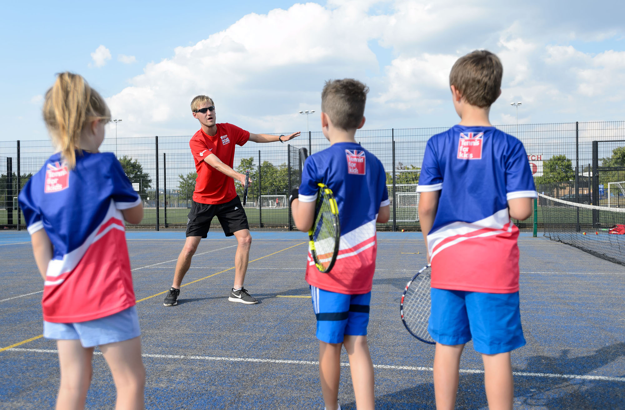 Coach demonstrating a forehand to children at a tennis session
