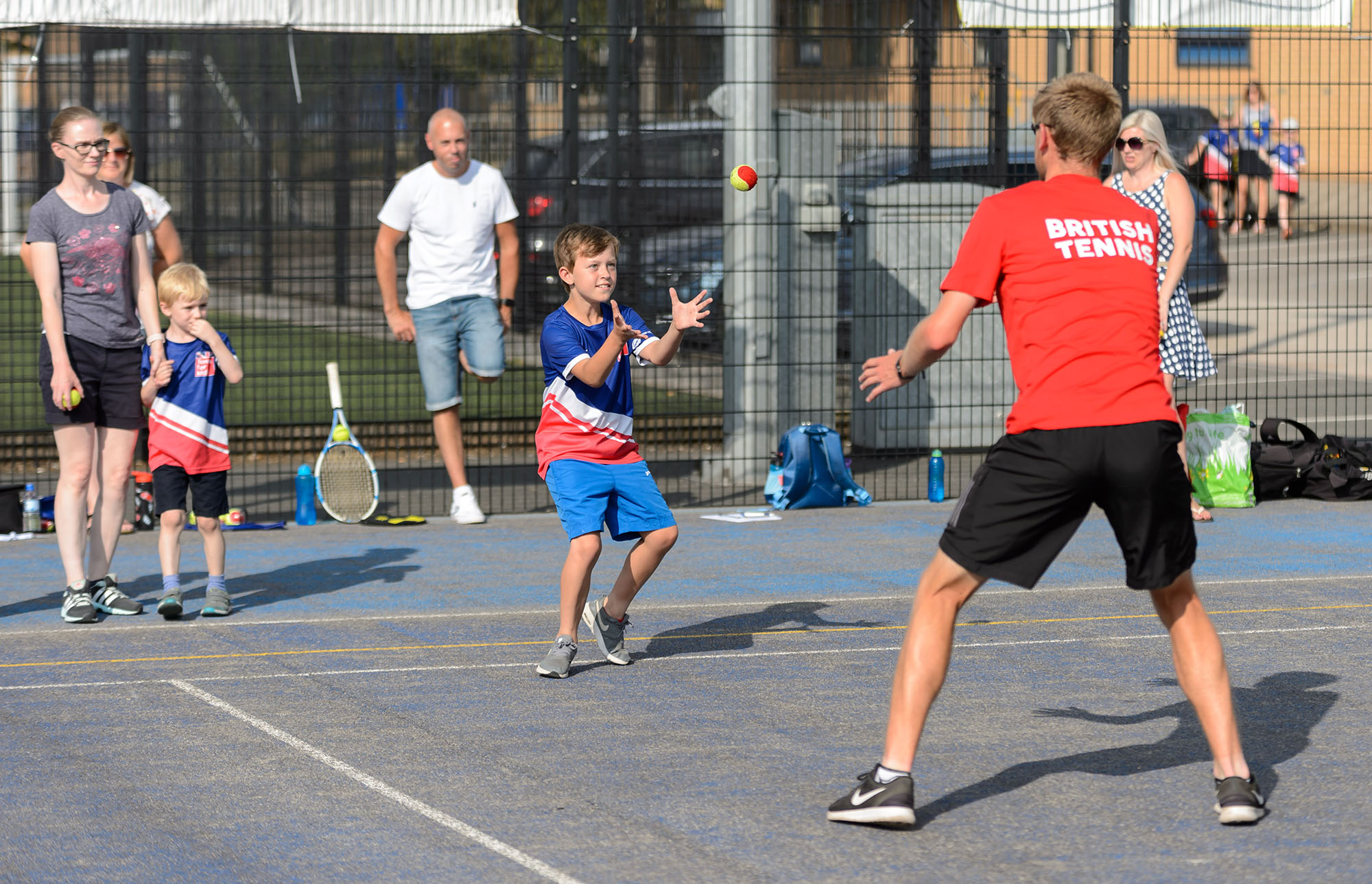 Coach throws a ball to a boy at a tennis session