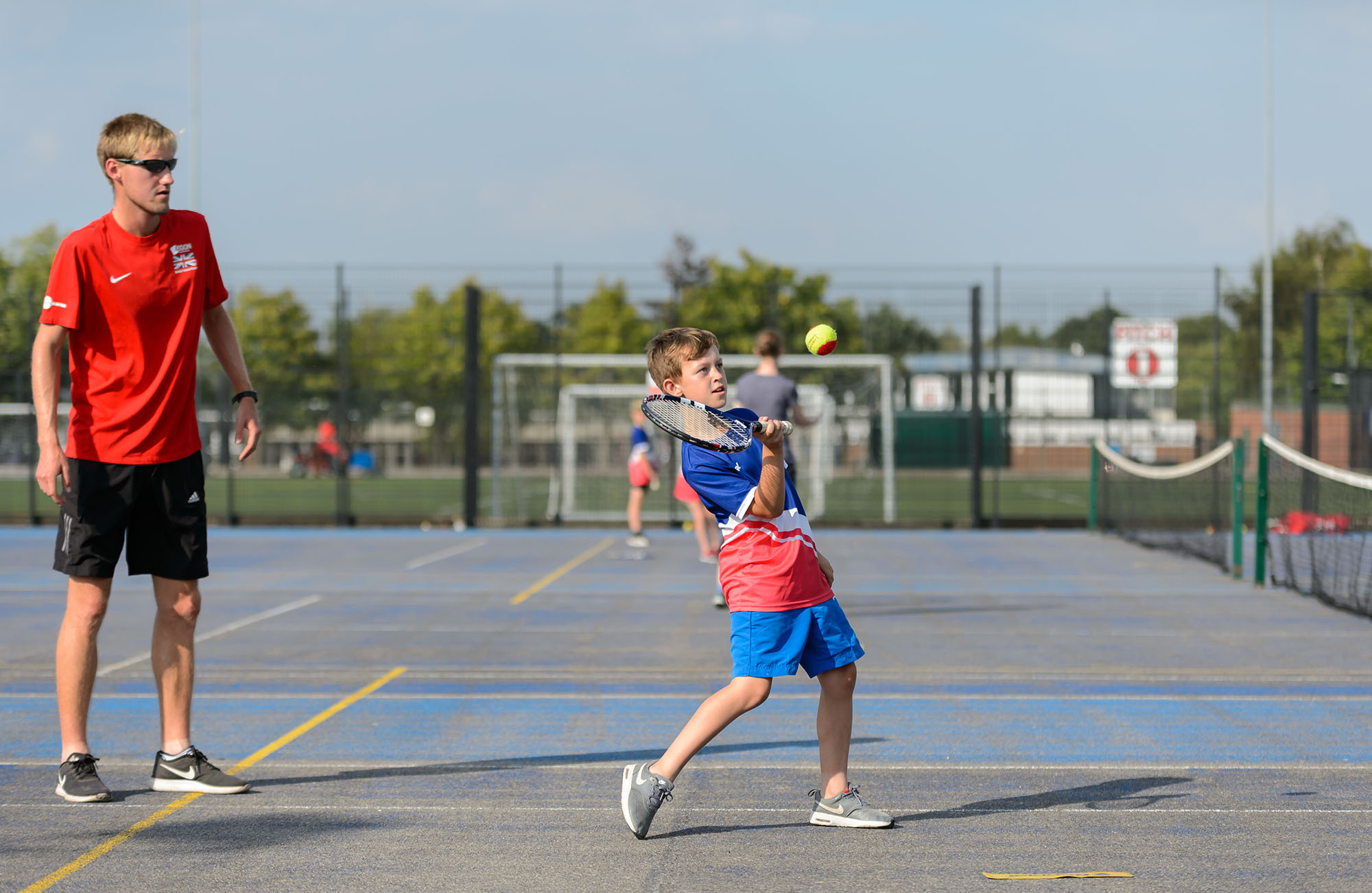 A boy playing a forehand as a coach looks on at a tennis session