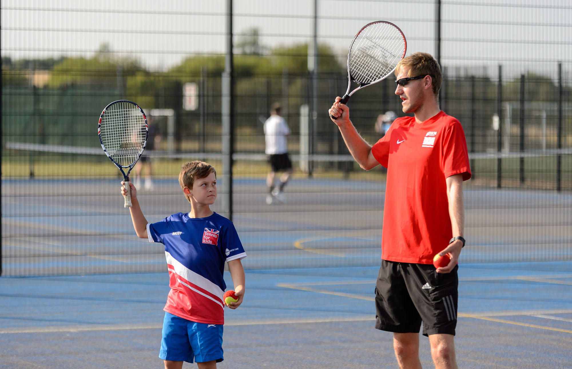 A coach demonstrates a serve to a boy at a tennis coaching session