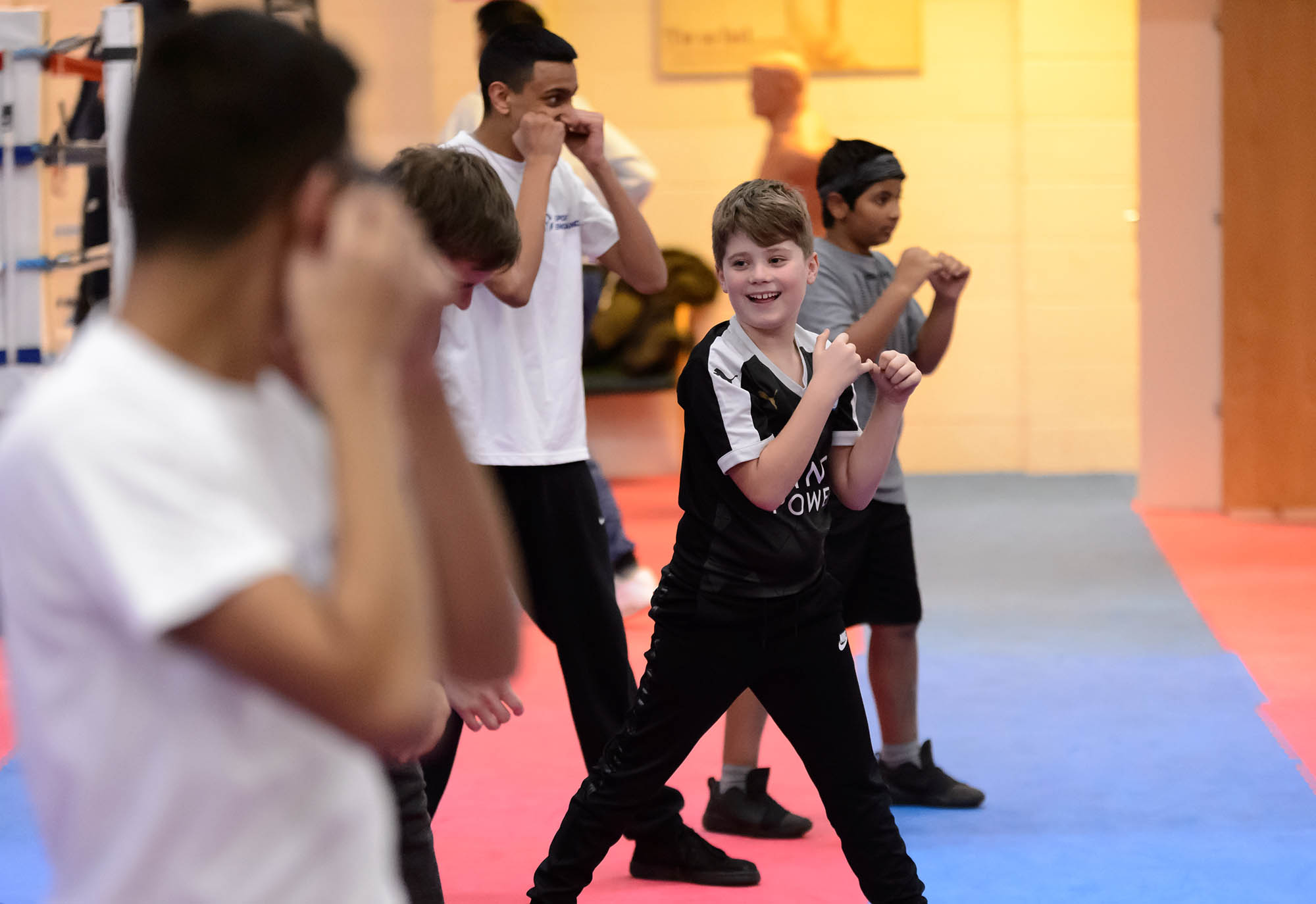 Young boys learning boxing from older boys in gym