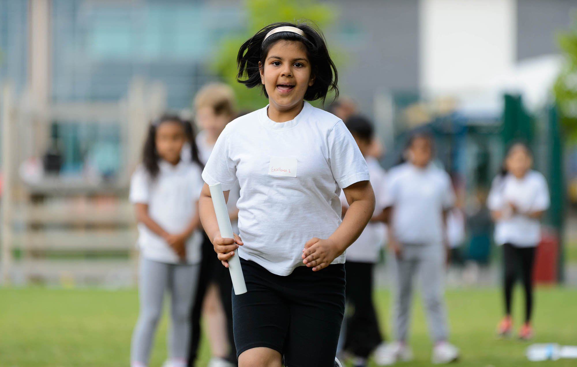 girl with relay baton running face on into camera