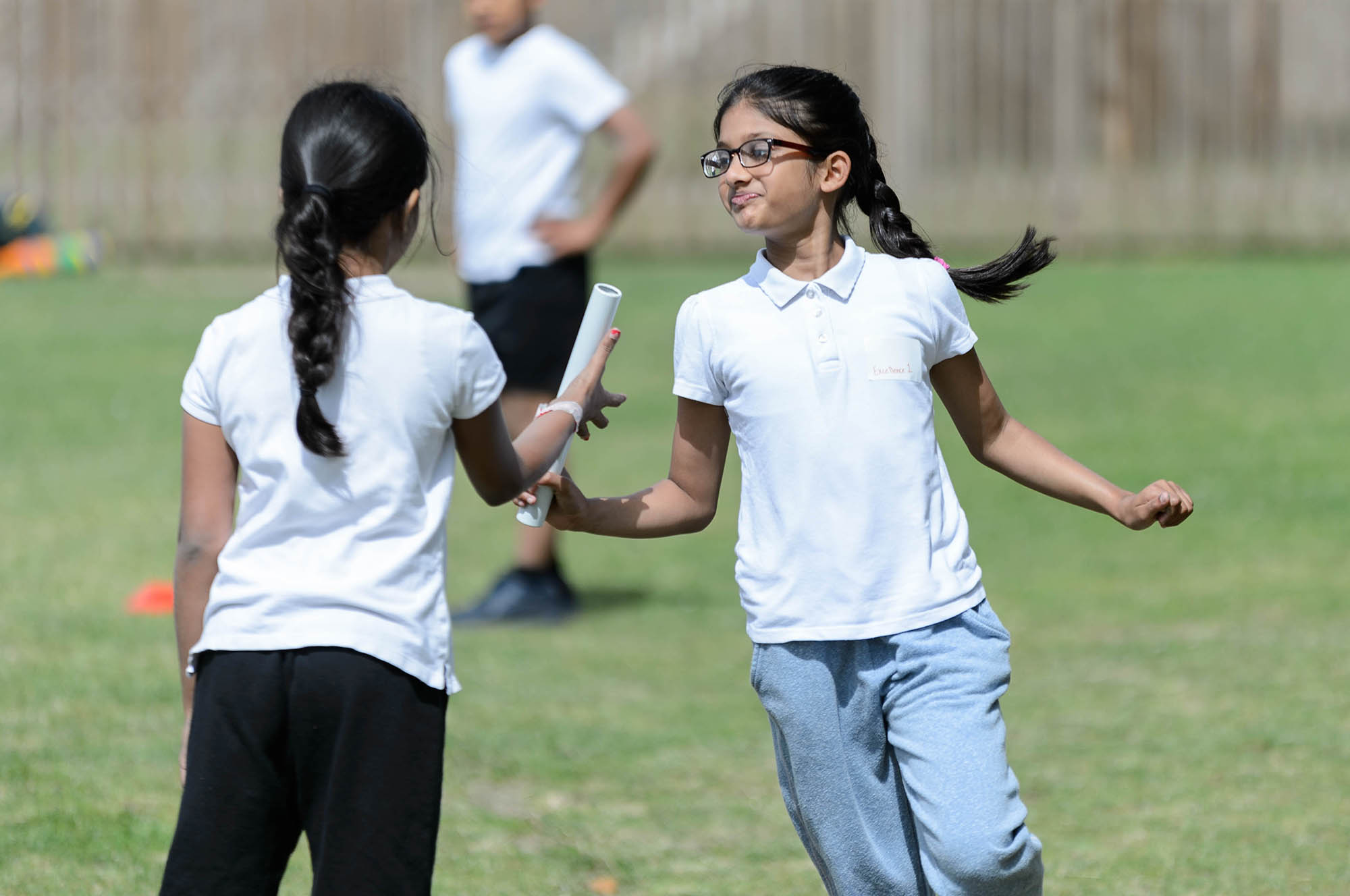 two girls running handing over baton in relay